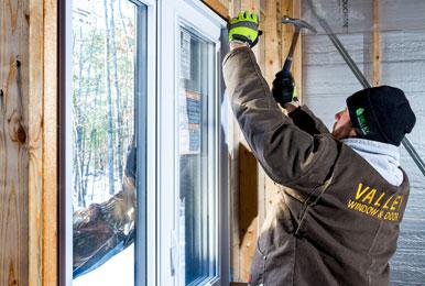 valley window and door crew installing a window in winter
