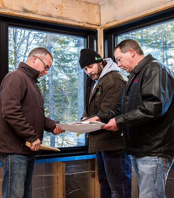 three men looking at house plans in new build