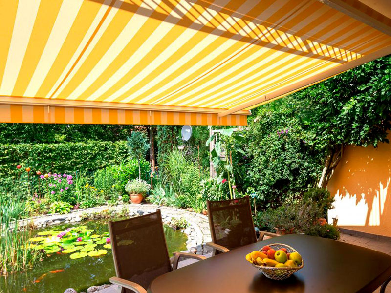 photo of retractable awning over backyard deck and pond