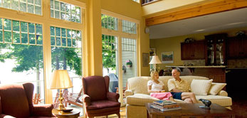 photo of couple sitting in family room featuring wall of windows