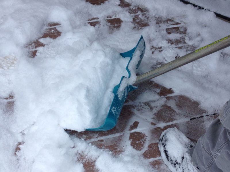 using a plastic shovel to remove snow from pvc vinyl decking boards